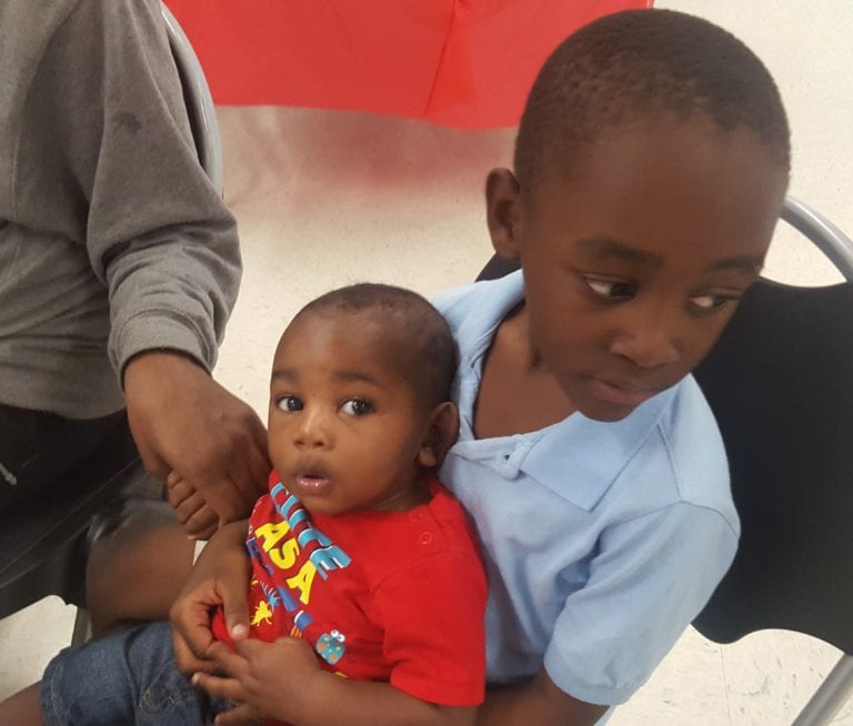 Kids sitting next to parent